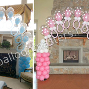 Balloon arch for baby shower made with blue and pink balloons shaped like baby bottles by balloon masters